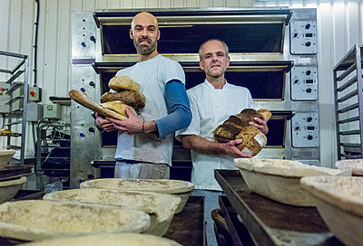 Bakers holding freshly-made bread - p429m1418239 by Seb Oliver