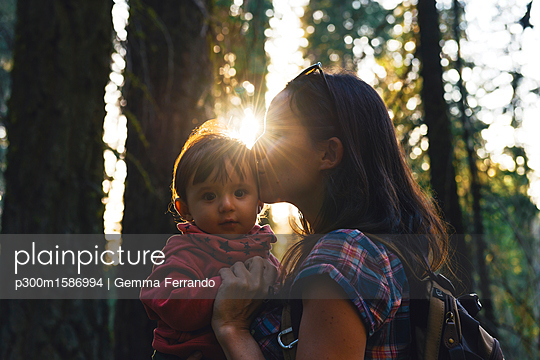 USA, California, Sequoia National Park, woman kissing her little daughter at sunset - p300m1586994 von Gemma Ferrando