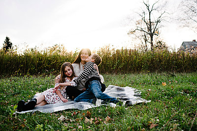 Brother kissing mother while sister sitting by her on picnic blanket at park - p1166m1555647 by Cavan Images