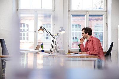 Man sitting at desk in office - p300m1460677 by Florian Küttler