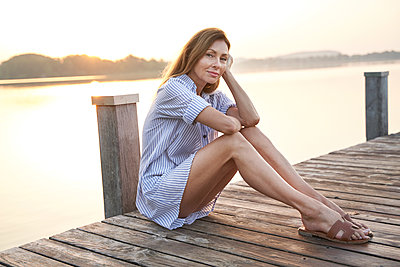 Portrait of mature woman sitting on jetty at a lake at sunrise - p300m2140975 by Philipp Nemenz