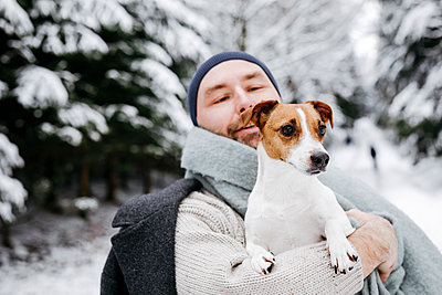 Man looking at Jack Russell Terrier dog during winter - p300m2256103 by Katharina Mikhrin