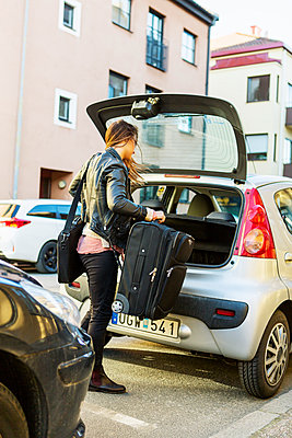Rear view of businesswoman loading luggage in car trunk on street - p426m1085545f by Kentaroo Tryman