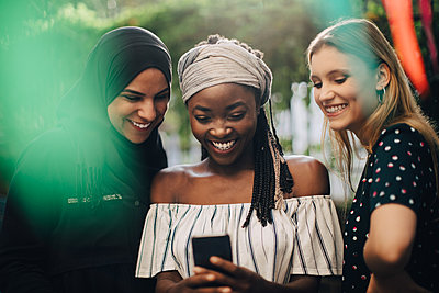 Smiling multi-ethnic female friends looking at mobile phone while standing in backyard - p426m2046247 by Maskot