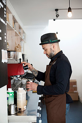 Side view of young male barista operating coffee maker in cafe - p426m927859f by Astrakan