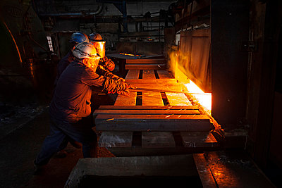 100mm square steel billet is removed from furnace as cold steel billet waits in foreground to be heated - p429m875672f by Charlie Fawell