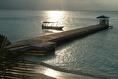 Jetty and a boat at sunset in the Caribbean - p855m2261356 by Natalie Tepper