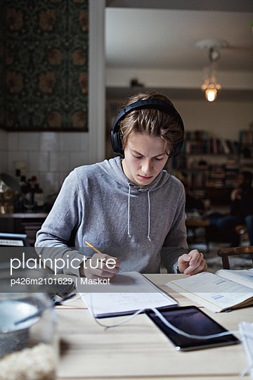 Studious teenage boy listening music while studying on table at home - p426m2101629 by Maskot