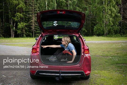 Boy Sitting In The Boot Of A Car   - p847m2104793 by Johanna Hanno