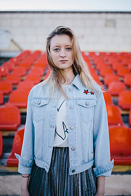 Portrait of girl in denim jacket on the background of spectator seats in the stadium - p1363m1332312 by Valery Skurydin