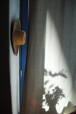 Straw hat hanging on the wall - p1648m2228454 by KOLETZKI
