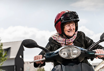 Active senior lady riding motor scooter in the city - p300m2030450 von Uwe Umstätter