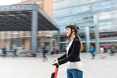 Woman riding e-scooter in the city, Berlin, Germany, Berlin, Germany - p300m2156874 by William Perugini