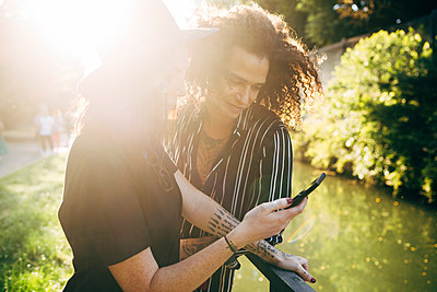 Couple using smart phone while standing in park on sunny day - p300m2206880 by Eugenio Marongiu