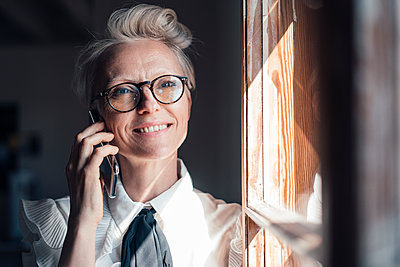 Smiling businesswoman with eyeglasses looking away while talking on smart phone at window in home office - p300m2267033 by Robijn Page