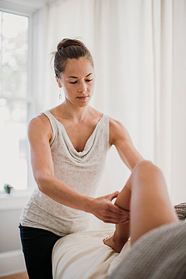 A young female massage therapist works on the legs of a patient - p1166m2107024 by Cavan Images
