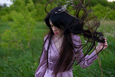 Woman in purple dress on a meadow - p1646m2257577 by Slava Chistyakov