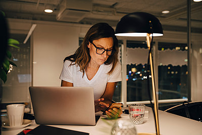 Confident female entrepreneur using smart phone while sitting with laptop at illuminated desk in workplace during night - p426m2194855 by Maskot