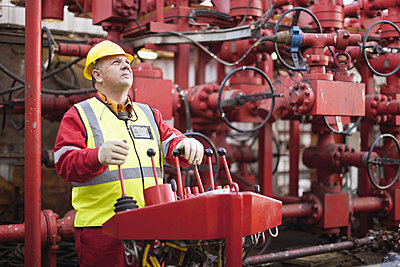 Worker operating machinery on oil rig - p42915049f by Hybrid Images