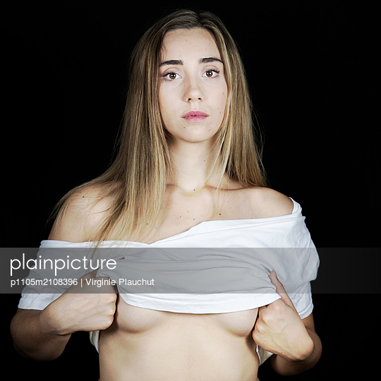 Young woman taking her clothes off - p1105m2108396 by Virginie Plauchut