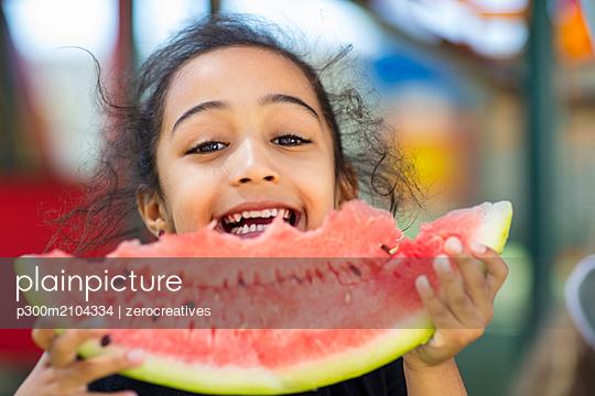 Portrait of happy girl eating a watermelon in kindergarten - p300m2104334 by zerocreatives