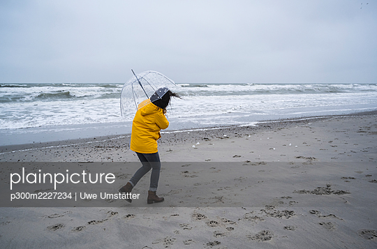 Woman in raincoat walking with umbrella at sea shore against sky - p300m2227234 by Uwe Umstätter
