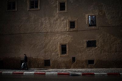 Man walking in street at night - p1007m1216789 by Tilby Vattard