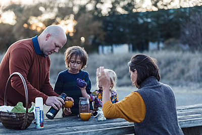 Family setting picnic table with hot chocolate during fall - p1166m2095139 by Cavan Images