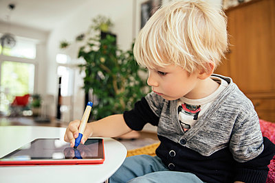 Little boy drawing with a digital pen on digital tablet at home - p300m1029110f by Mareen Fischinger