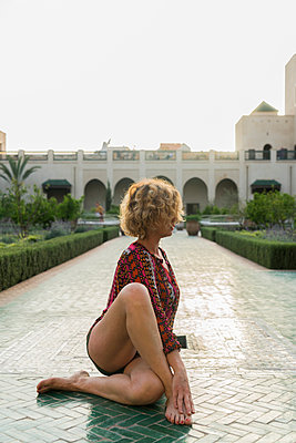 Morocco, Marrakesh, tourist sitting on the floor in a courtyard doing yoga - p300m1450239 by Kike Arnaiz