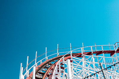 Low angle view of roller coaster track against clear blue sky - p301m1101973f by Sebastian Doerken