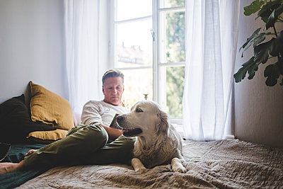 Dog resting on bed while senior man reading book against window at home - p426m2046390 by Maskot