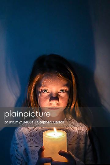 Portrait of girl holding a candle - p1019m2134681 by Stephen Carroll