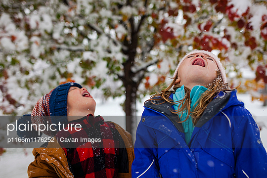 Playful siblings sticking out tongue while standing outdoors during winter - p1166m1176252 by Cavan Images