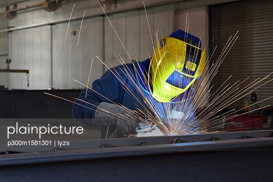 Welder at work in factory - p300m1581301 von lyzs