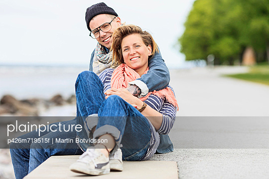 Portrait of happy couple sitting at the edge of a wall