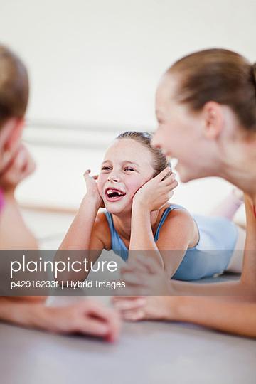 Ballet dancers talking on studio floor