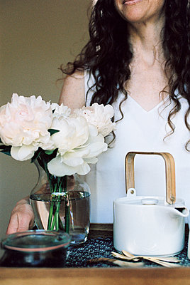 Woman carrying a tray with a teapot and a vase of white roses. - p1100m1080254 by Mint Images