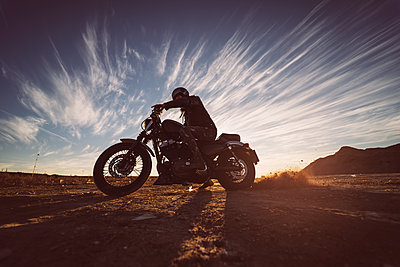Man on motorbike in nature at sunset - p300m2104284 by Oscar Carrascosa Martinez