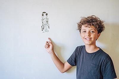 Portrait of smiling boy pointing to a drawing on a whiteboard - p300m2140236 von Javier De La Torre Sebastian