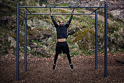 Full length of man exercising on monkey bars at outdoor gym - p426m1468584 by Maskot