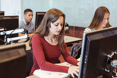 Young female student using computer while sitting with friends in library at high school - p426m2072253 by Kentaroo Tryman