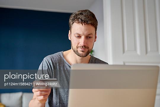 Junger Mann am Laptop mit Kreditkarte - p1124m1589421 von Willing-Holtz
