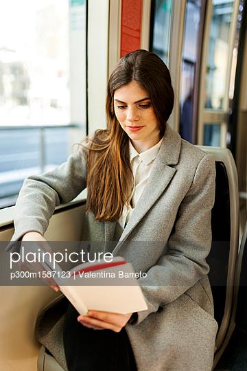 Portrait of young woman reading book in tramway - p300m1587123 von Valentina Barreto