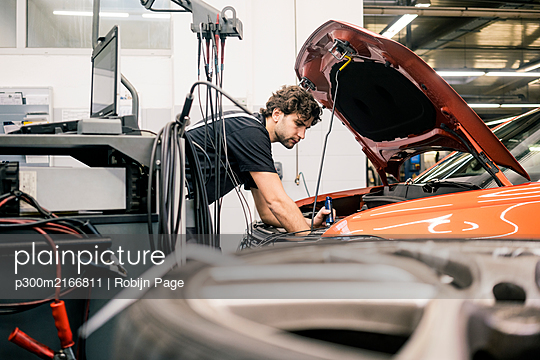 Car mechanic in a workshop working at car - p300m2166811 by Robijn Page