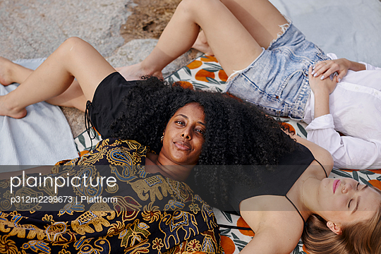 Three friends lying on blanket - p312m2299673 by Plattform