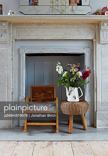 Cut flowers on stool with child's rocking chair in recessed marble fireplace of Colchester family home;  Essex;  England;  UK - p349m919976 by Jonathan Birch