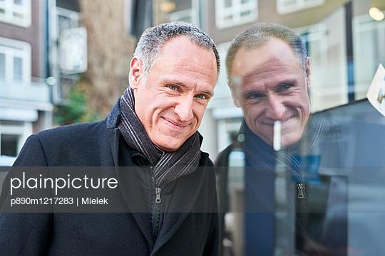 Mann mit Spiegelung in Glasscheibe - p890m1217283 von Mielek