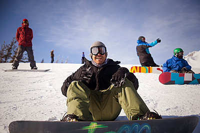 Cheerful friends with snowboarding on snowy field against sky - p1166m1209754 by Cavan Images