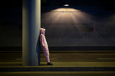 Young man in unicorn costume is waiting in the tunnel - p1221m2065311 by Frank Lothar Lange